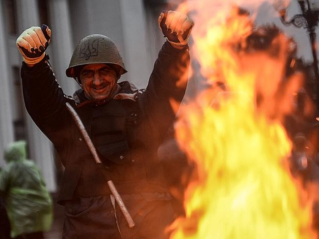An anti-government activist ... reacts after the vote of the Ukrainian Parliament to hold