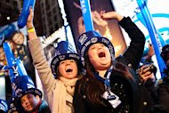 """Revelers cheer behind police barricades in Times Square in anticipation of midnight on New Year's Eve, Saturday, Dec. 31, 2011, in New York. Some revelers, wearing party hats and """"2012"""" glasses, began camping out Saturday morning, as workers readied bags stuffed with hundreds of balloons and technicians put colored filters on klieg lights. (AP Photo/John Minchillo)"""