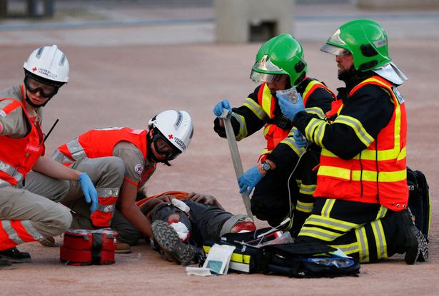 Rescuers take part in a mock attack drill in the fan zone in the centre of Lyon
