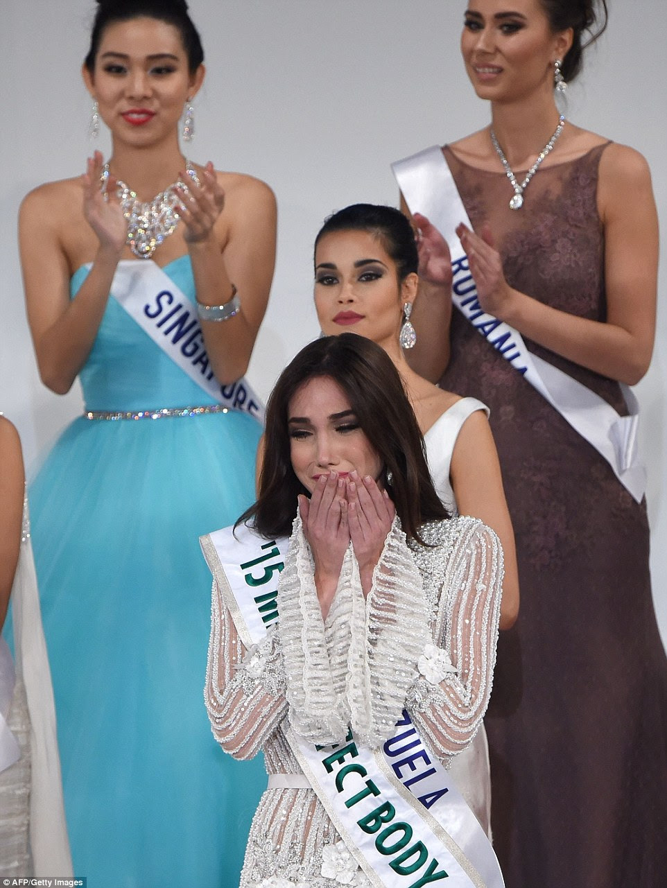 Miss Venezuela bursts into tears as she is announced as Miss International 2015. Miss Singapore, Miss Romania and another contestant do their best to smile and applaud for the camera behind her