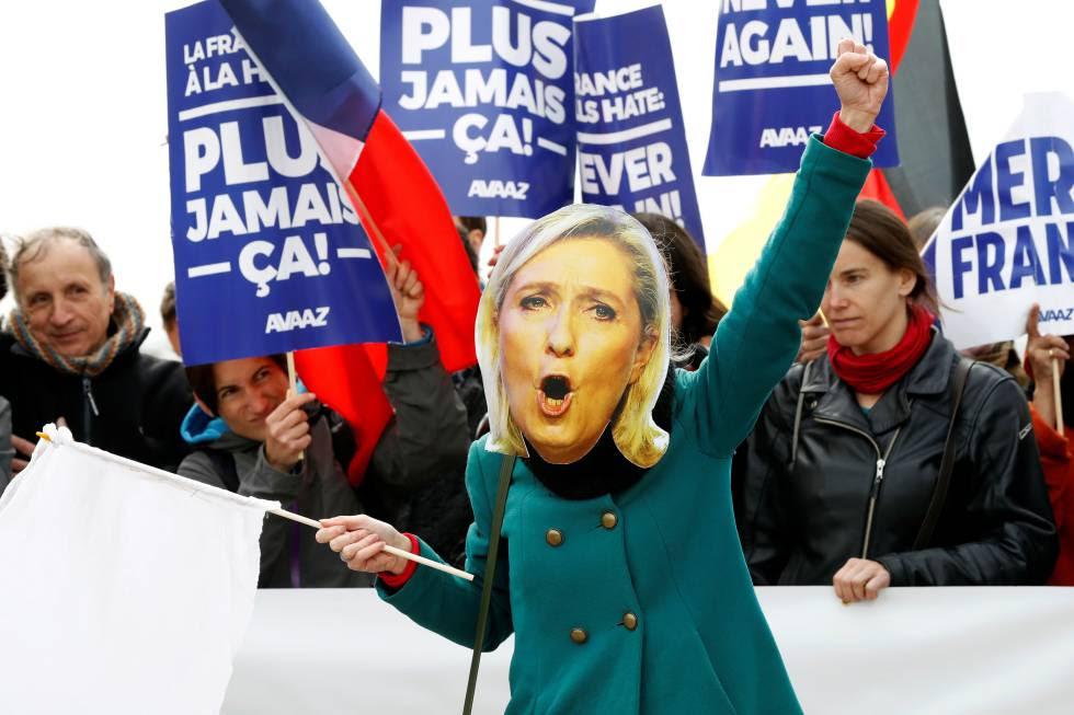 Una mujer con una máscara de Marine Le Pen en un mitin en París.