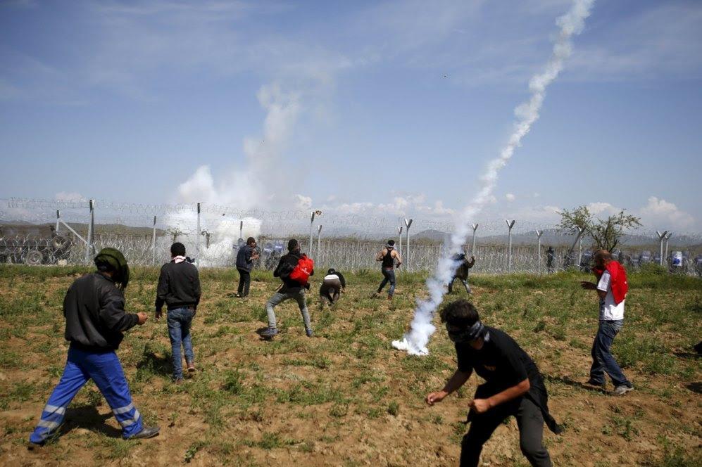 Varios participantes en la protesta tratan de esquivar el gas lanzado desde el otro lado de la alambrada.