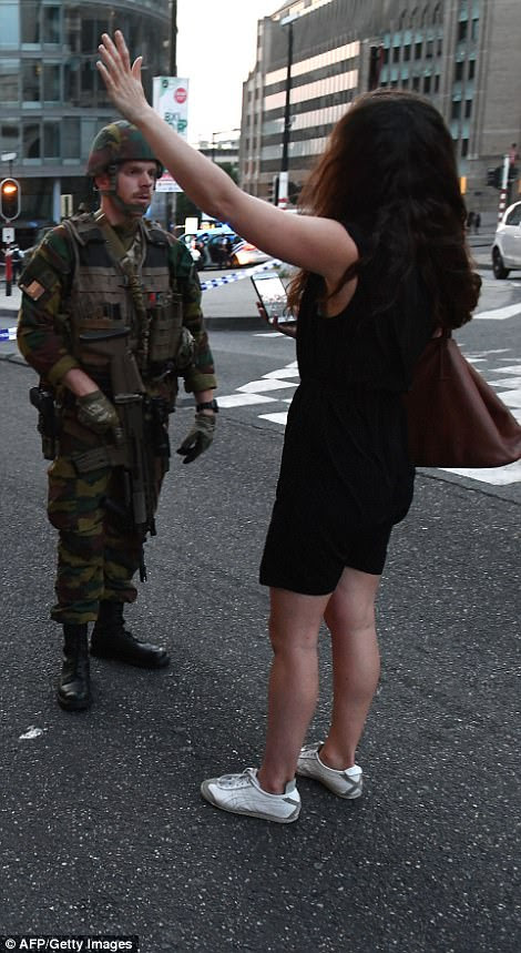 A panicked woman waves her arms as she gets the attention of an armed soldier outside