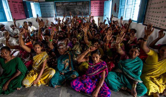 Mujeres de la comunidad de Veekajinipalli levantan la mano cuando se les pregunta si han padecido enfermedades de transmisión hídrica.