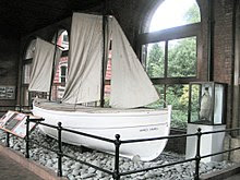 """White-hulled small boat sitting on a base of stones behind a rail, within a museum. The name """"James Caird"""" is visible. A stuffed penguin in a glass case stands nearby."""
