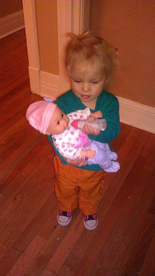 My granddaughter practices nurturing relationships with her first ever doll.