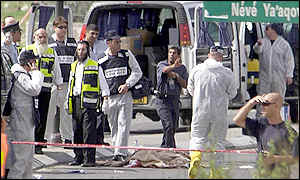 Israeli investigators near the covered body of a suspected Palestinian suicide bomber