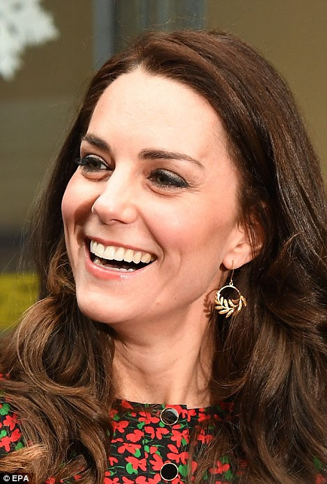 An animated Kate laughs as she gets into the swing of things at a charity Christmas party