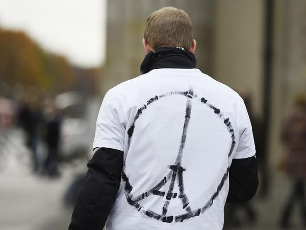 "A man wears a shirt with the ""Peace for Paris"" symbol, near the French embassy in Berlin on Saturday, a day after the deadly attacks in Paris."
