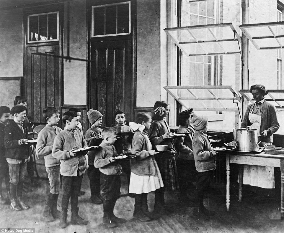 Children waiting in line for food at an open air school in Manhattan, New York City, circa 1900