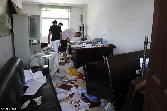 Ransacked: Demonstrators stand inside a destroyed office at the local government building where desks and computers were overturned and smashed