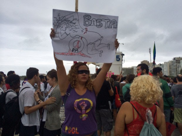 Mulher levanta cartaz que remete ao estupro de PMs (Foto: Lívia Torres / G1)
