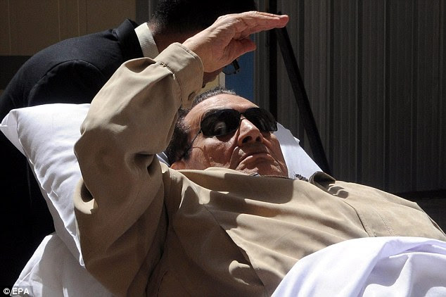 Ousted Egyptian president Hosni Mubarak attempts to cover his face as he is wheeled into an ambulance after being found guilty
