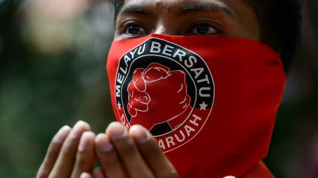 """A pro-government 'red shirt' protestor prays with a face mask which reads read """" Malay United"""" on the face, at a pro-government demonstration in Kuala Lumpur this month."""