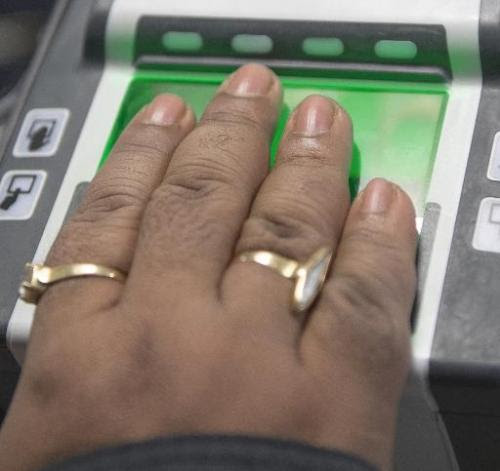 An international traveler scans in their hand on a US Customs and Border Protection fingerprint scanner at Dulles Airport on Feb