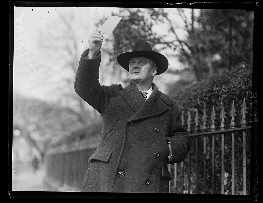 The wheels of the great government machine and of private business marked time today while thousands of employees and the departmental heads viewed the eclipse. Postmaster General New snapped as he was watching the eclipse with the aid of a photographic plate. Photo by Harris & Ewing, 1925 January. ttp://hdl.loc.gov/loc.pnp/hec.44777