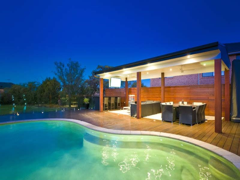 Freeform pool design using tiles with decking & decorative ...