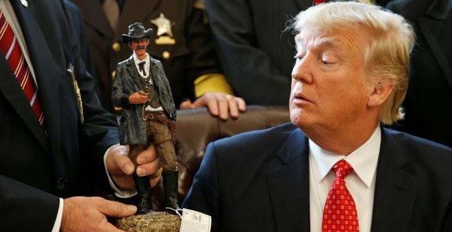 Trump recibe una figura de un sheriff durante una reunión en la Casa Blanca. REUTERS/Kevin Lamarque