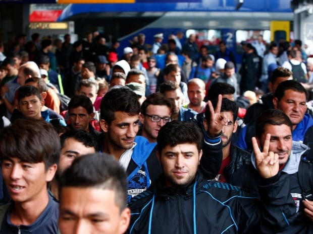 Refugees walk on the platform after arriving by train at the main railway station in Munich on Sunday, Sept. 13, 2015. Germany will introduce temporary border checks on the Austrian frontier in a bid to limit the influx of refugees, the interior minister said.