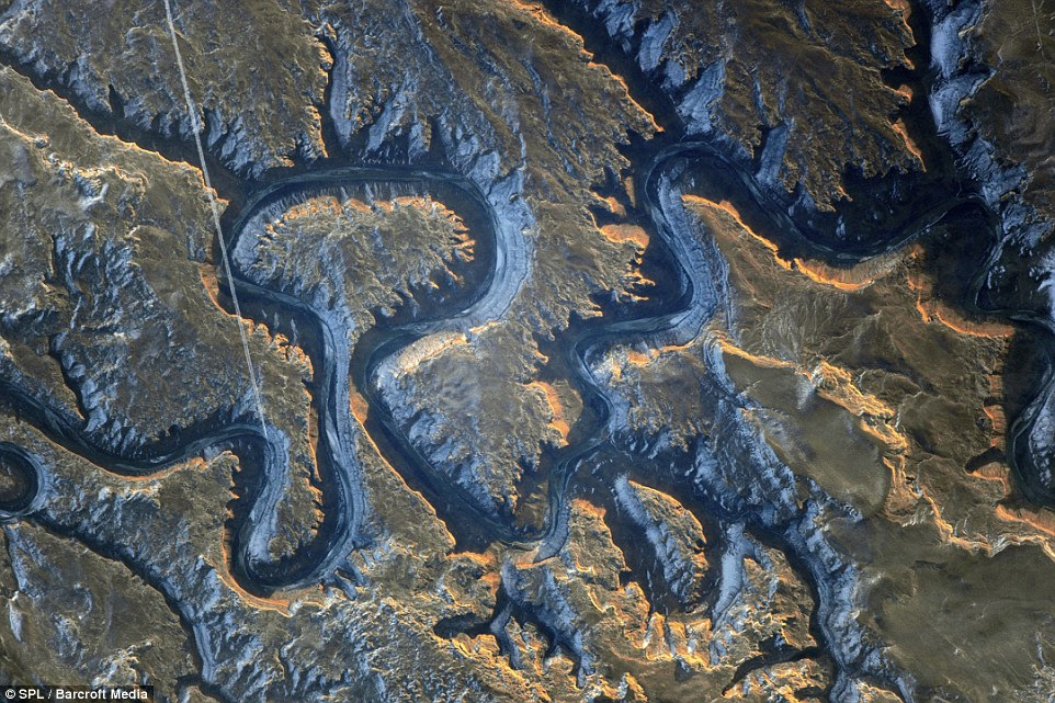 Green river canyon shadows: Also known as Bowknot Bend, its steep cliffs are up to 985ft (300 metres) high and cast a shadow on the river below. At lower left is a contrail caused by a flying aircraft