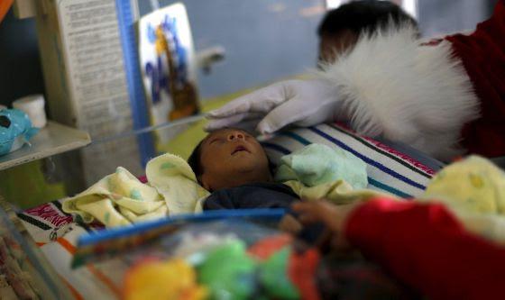 Un hombre vestido como Santa Claus acaricia a un bebé en un hospital guatemalteco el pasado 16 de diciembre.