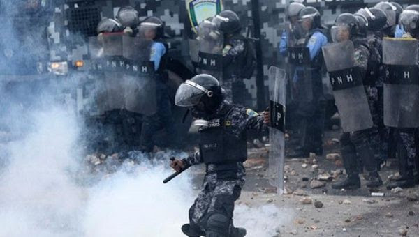 Riot police throw tear gas at protesting students in Honduras, July 25, 107.
