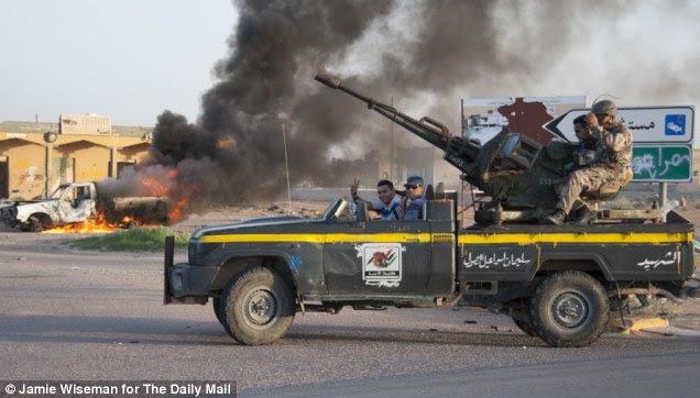 Los combatientes rebeldes en Tarwegha, al sur de Misrata, que ha sido sistemáticamente saqueados y destruidos desde la caída de Gadafi