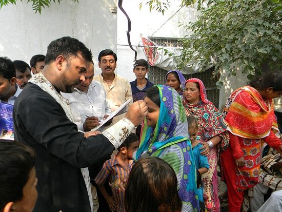 Fr. Adrian chrismating Orthodox Pakistanis. Photo from the church's facebook cite.