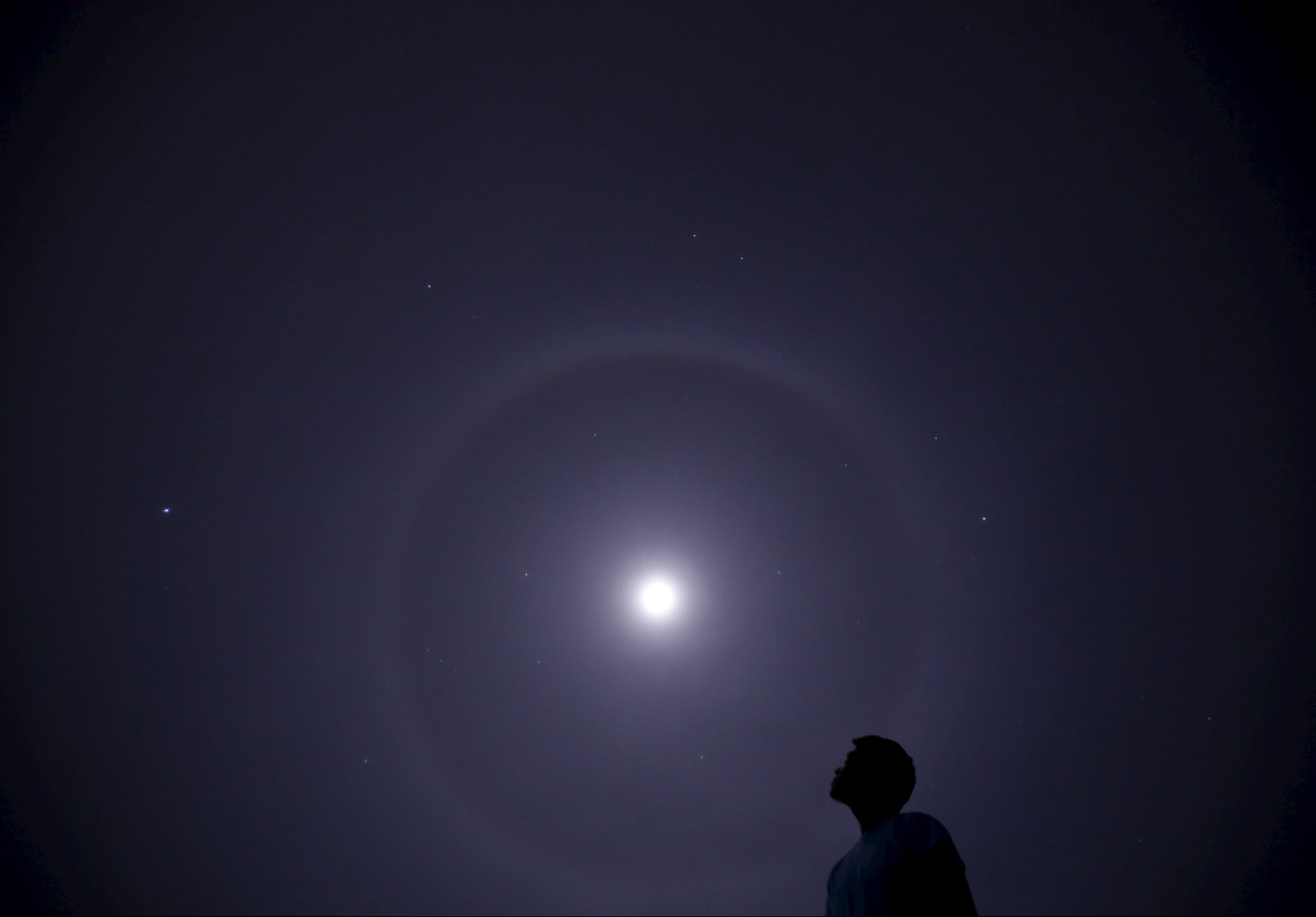 A man looks towards a lunar halo seen above the sky of Kathmandu...A man looks towards a lunar halo seen above the sky of Kathmandu, Nepal, March 15, 2016. REUTERS/Navesh Chitrakar
