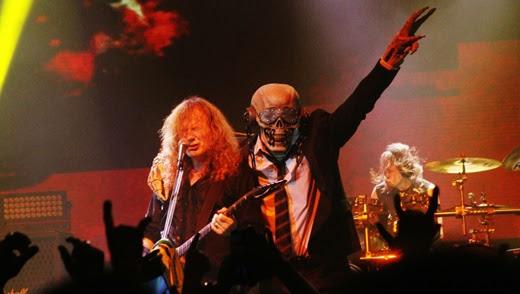 O mascote Vic Rattlehead, na segunda entrada no palco, abraça Mustaine, durante 'Peace Sells'