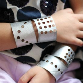 Turn paper rolls into super cool bracelets for kids using a hole puncher, silver paint and some yarn!