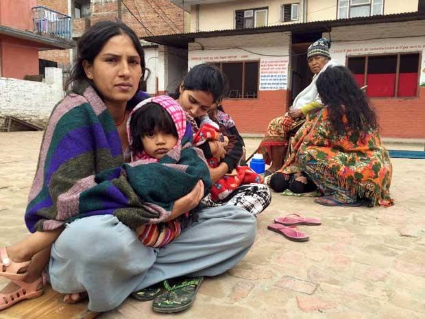 Mães e filhos deixam suas casas e esperam em uma escola após forte terremoto atingir o Nepal e a Índia. (Foto: Navesh Chitrakar / Reuters)