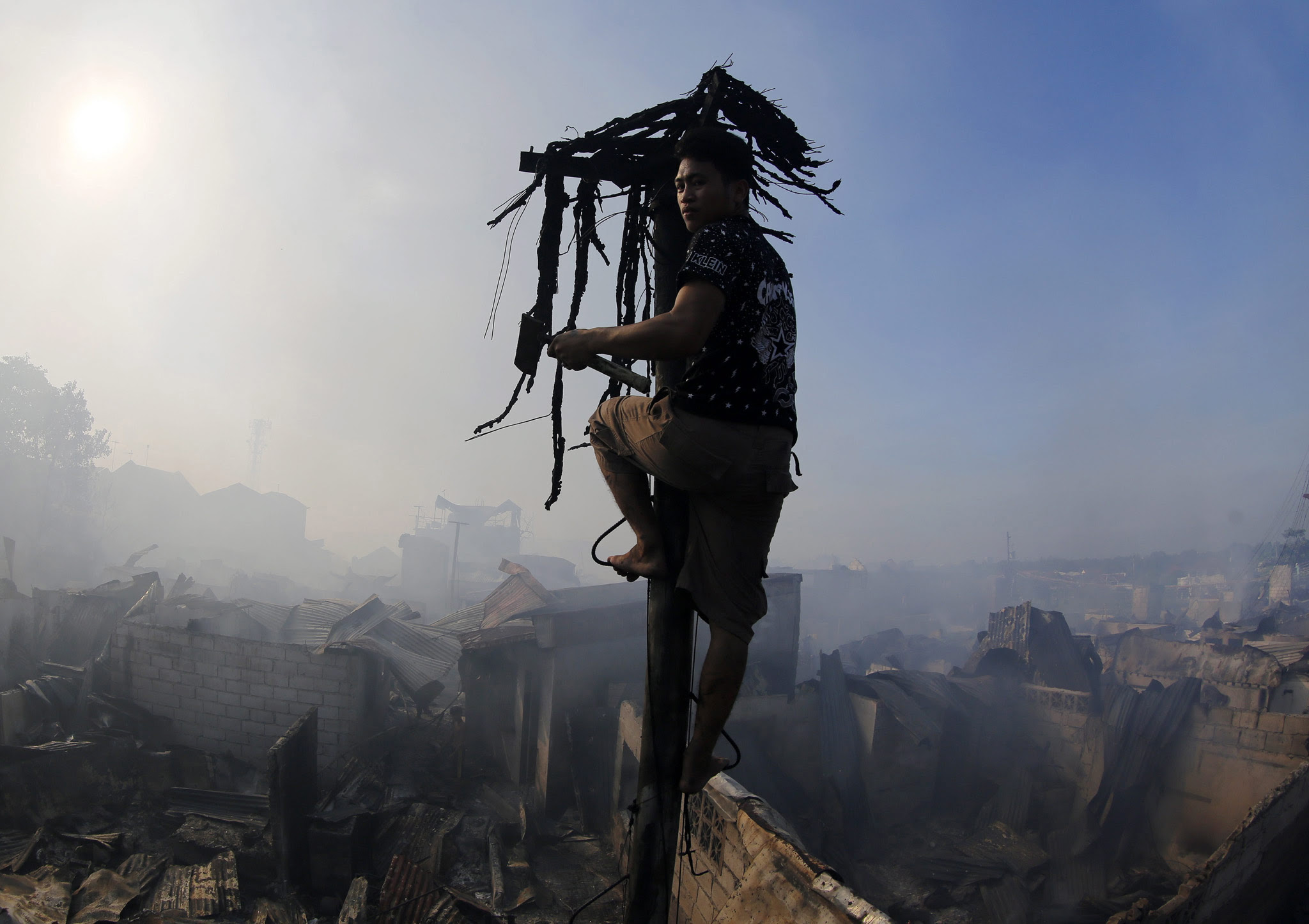 A Filipino fire victim climbs a burnt electric post following a fire that broke out before dawn on All Souls Day in Las Pinas city, south of Manila, Philippines