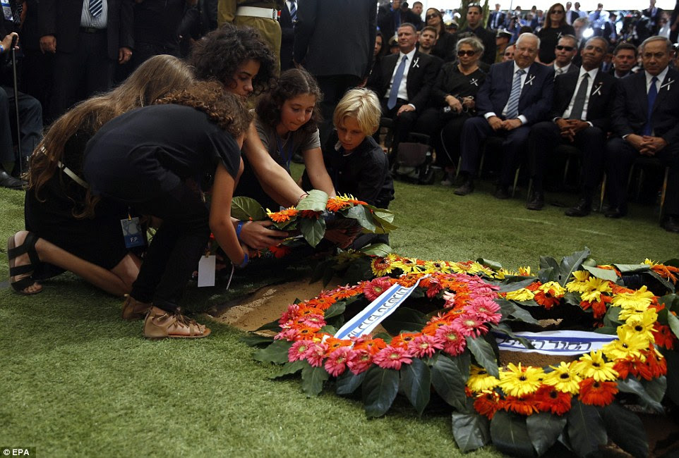 Pungente: Os netos de Shimon Peres colocar uma coroa de flores no túmulo de seu avô durante a cerimônia de enterro como um presidente Obama olha e sorri tristemente