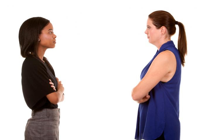 Black woman and white woman facing each other.