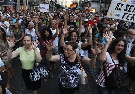Protesters raise their arms during a demonstration against government austerity measures in central Valencia, July 19, 2012. REUTERS/Heino Kalis. by Pan-African News Wire File Photos