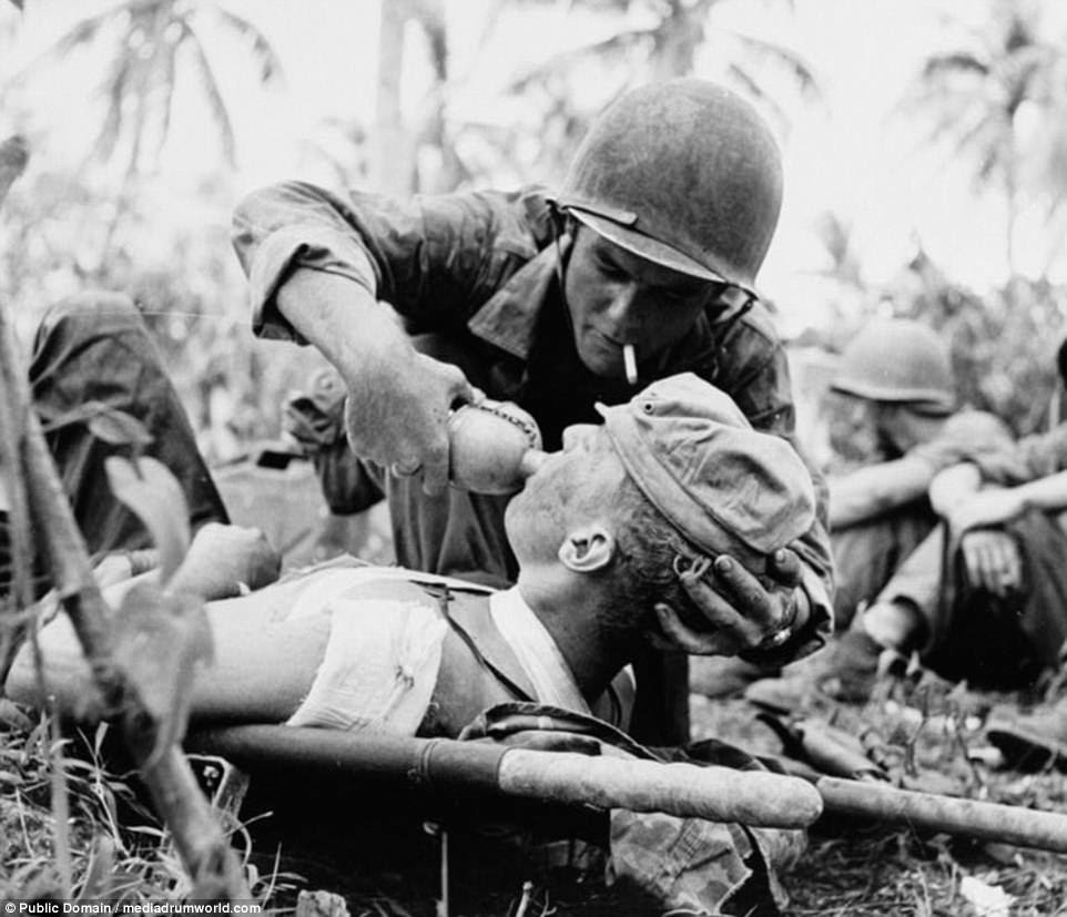 Pictured: A US Marine is given water as he lies on a stretcher with bandages covering his wounds after seeing action during the 1944 Battle of Guam. The island Guam is thought to have first been settled by humans in 2,000BC when people from South East Asia managed to get there in small boats. The original inhabitants are known as theChamorro. They flourished for nearly three and a half millennia before the island was discovered by Europeans when Portuguese explorer Ferdinand Magellan arrived on the island in 1521