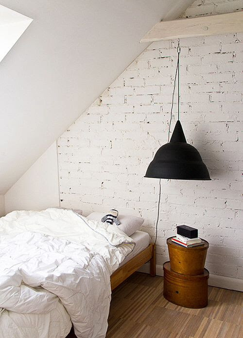 White brick wall, dangling black pendant