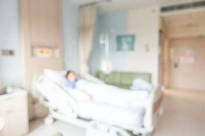 Imagem distorcida mostra leito de hospital ocupado por um paciente.
