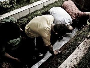 Amigos se debruçam sobre o corpo durante o enterro (Foto: Gabriel Chaim/G1)