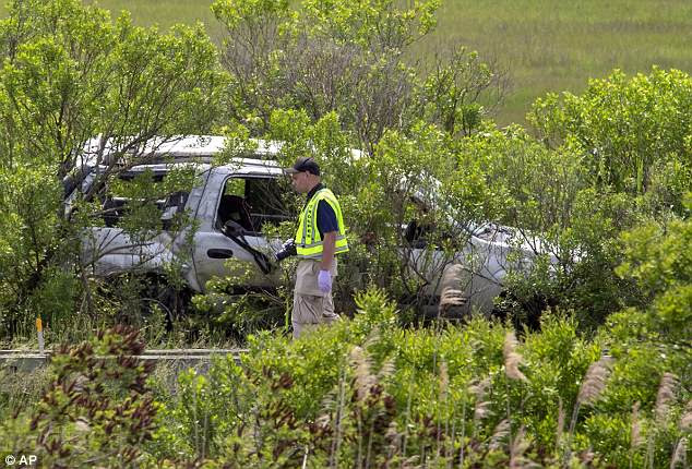 Investigators work at the scene of the crash where three teenagers died on Friday. The stolen SUV had 10 people inside, including an 18-month-old baby, when it flipped several times after its 15-year-old female driver lost control