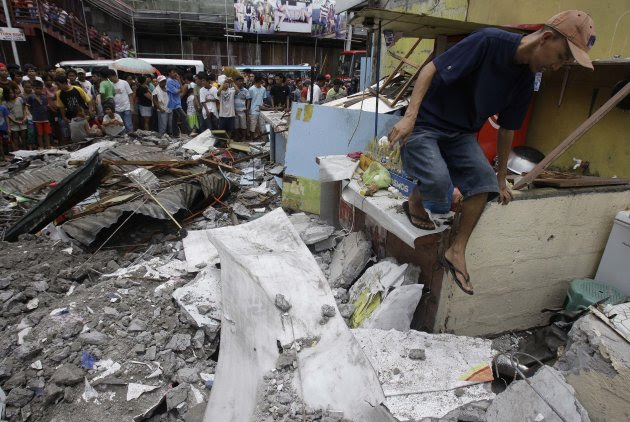 A man walks along the rubble of a collapsed wall as it was knocked down by strong winds, killing one man and injuring two others in suburban Novaliches, Quezon City, Philippines, Sunday, Aug. 28, 2011