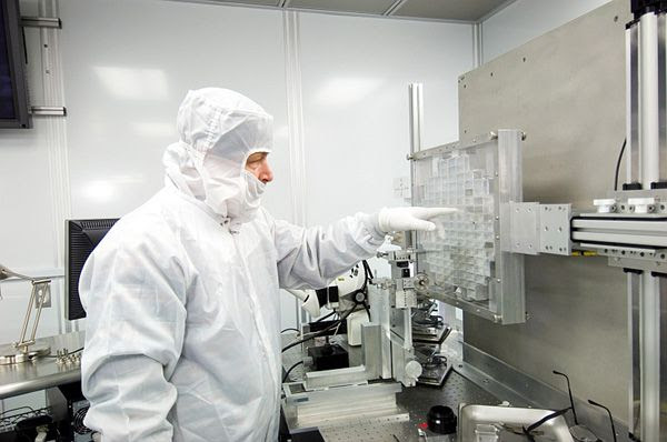 A scientist points at the location of one of the interstellar dust particles that impacted Stardust's aerogel collectors during their journey in space.