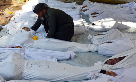 A man holds the body of a dead child among bodies of people activists say were killed by nerve gas