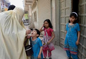 A health worker administers polio vaccine to a child …