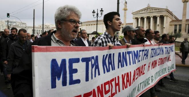 Varios activistas del sindicato comunista PAME corean consignas durante la huelga general de 24 horas contra los últimos recortes pactados con la UE. EFE/Alexandros Vlachos
