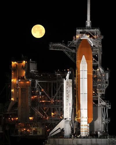 A full moon shines above space shuttle DISCOVERY at Launch Complex 39A, during the early morning hours of March 11, 2009.