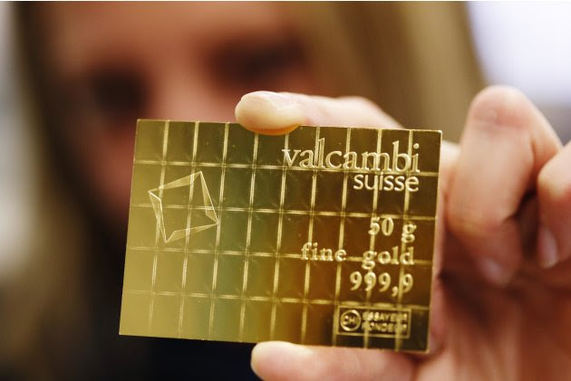 An employee shows a gold Combibar at a plant of gold refiner and bar manufacturer Valcambi SA in the southern Swiss town of Balerna