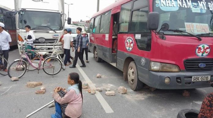 Tức giận vì thiếu đường gom dân sinh, nhiều người dân đã mang vật cản ra chặn xe trên đường Bắc Thăng Long-Nội Bài. (Hình: báo Thanh Niên)