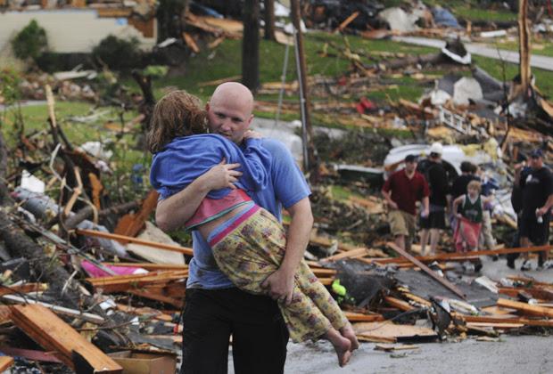 Homem socorre jovem garota que teve a casa atingida pelo tornado na cidade de Joplin (Foto: AP)